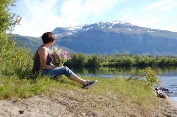 Dame med blomterbukett ved elva