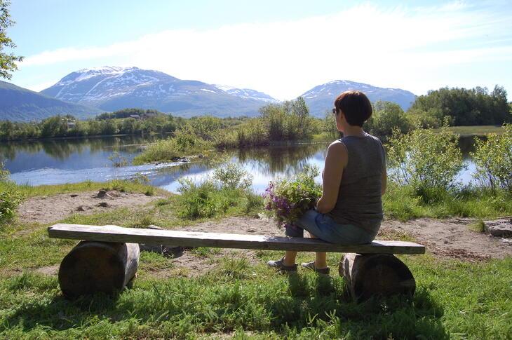 Dame med blomsterbukett ved elva