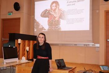 Terapeut ved Viken senter Mirja Päiviö sitter foran et bilde av en samisk kvinne med teksten Å uttrykke følelser uten ord